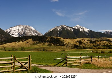 Beautiful view of a piece of a ranch with snowy mountains as a backdrop on a spring day