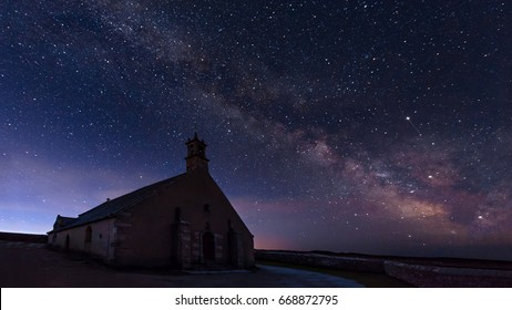 """Beautiful view of """"Pointe du van"""" on a wonderful cloudless night with light on and milky way on the background"""