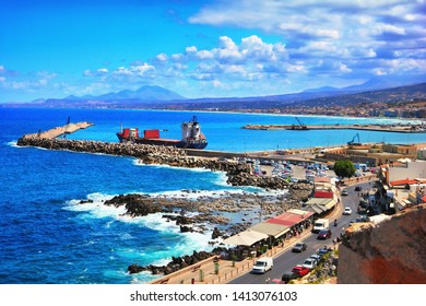 Beautiful view - port, ship, pier, city street, cars, bright blue water of Mediterranean sea, surf, at the background of distant mountain and shore in Rethymno, Crete island, Southern Greece, Europe