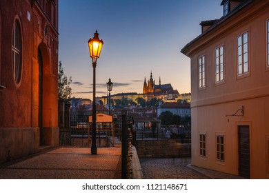 Beautiful view of Prague Castle at sunset from a historical street with gas lamps over the river Vltava. Prague