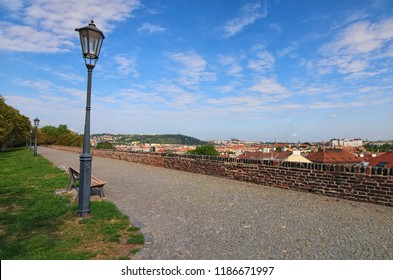 """Beautiful view of Prague from park in Vysehrad (""""Upper Castle""""). Buildings with red tile roofs, a lot of trees. Colorful vibrant sky. Summer landscape photo on a sunny morning. Prague, Czech Republic."""