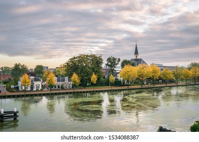 Beautiful view of the river Rhine in Alphen aan den Rijn, Netherlands with historic church and trees in autumn foliage