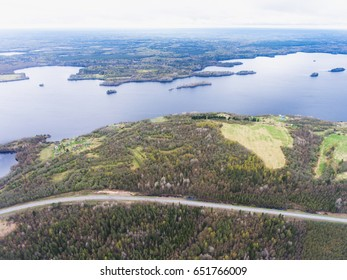 Beautiful view from a road going through the beautiful lake and forest, surrounded with water on both sides, shot above from drone, aerial vibrant picture