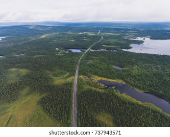 Beautiful view from a road going through the beautiful lake and forest, surrounded with water on both sides, shot above from drone, aerial vibrant picture, Murmansk Oblast, Russia