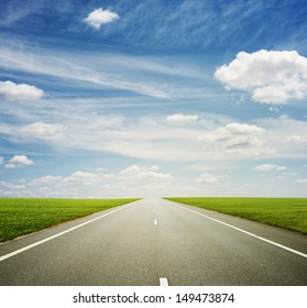 beautiful view of roadway, green field and blue sky