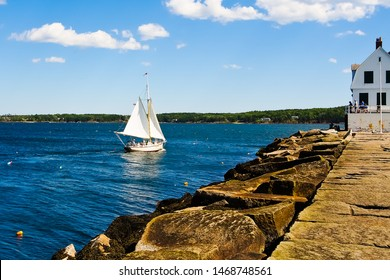 Beautiful view of Rock paved path to Rockland breakwater lighthouse and sailing boat in Rockland harbor Maine usa