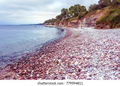 Beautiful view of rocky coast on Gotland, island in the Baltic Sea in Sweden. Smooth round colorful stones. The coastline on the background. Pink and violet filter.
