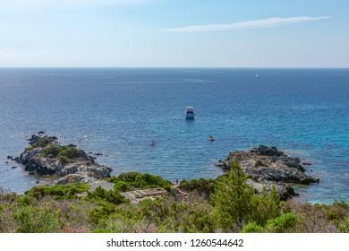 Beautiful view of the rocky shore of Elba Island, blue sea and boats. Elba island, Tuscany, Italy