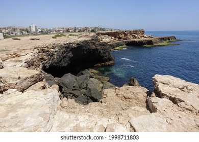 A beautiful view of a rocky shore near a calm sea under a clear sky at the Locos Beach in Torrevieja, Spain