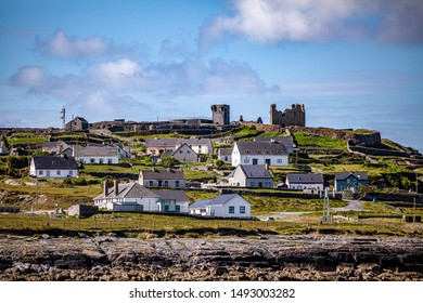 Beautiful view of the ruined 15th century castle in a prehistoric stone fort and houses on the Inis Oirr island seen from a boat, wonderful sunny day in the Aran Islands, Ireland