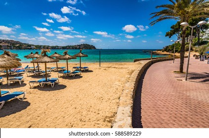 Beautiful view of the sand beach with sun umbrellas and sunbeds in Santa Ponsa, Majorca Spain, Mediterranean Sea, Balearic Islands.