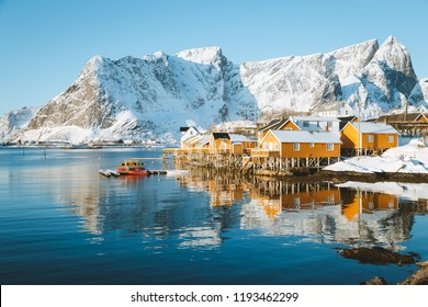 Beautiful view of scenic Lofoten Islands archipelago winter scenery with traditional yellow fisherman Rorbuer cabins in the historic village of Sakrisoy at sunrise, Norway, Scandinavia