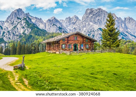 Beautiful view of scenic mountain landscape in the Alps with traditional old mountain chalet and fresh green meadows on a sunny day with blue sky and clouds in spring