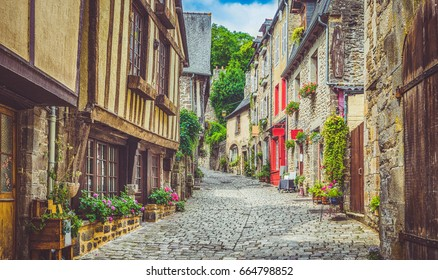 Beautiful view of scenic narrow alley with historic traditional houses and cobbled street in an old town in Europe with blue sky and clouds in summer with retro vintage Instagram grunge filter effect