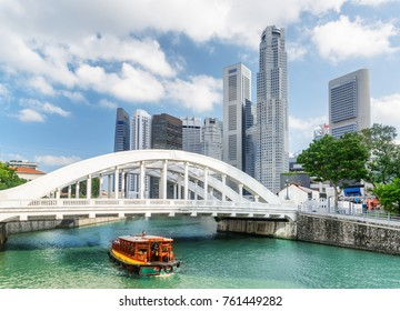 Beautiful view of scenic white bridge and traditional wooden tourist boat sailing along the Singapore River with azure water. Amazing skyscrapers of downtown are visible on blue sky background.