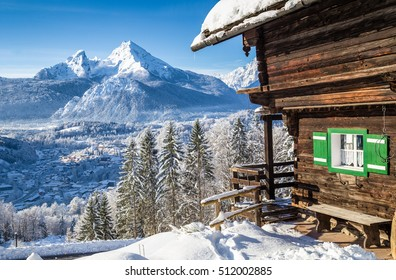 Beautiful view of scenic white winter wonderland mountain scenery in the Alps with traditional mountain chalet on a cold sunny day with blue sky and clouds