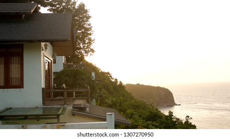 Beautiful view of the sea bay and a house in resort in mountains during amazing sunset.