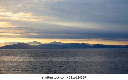 A beautiful view of the sea and the coast is far away on the horizon in Greece from Corfu in the evening light