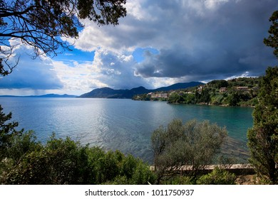 A beautiful view of the sea and the coast of the island of Corfu through pine branches on a sunny summer day