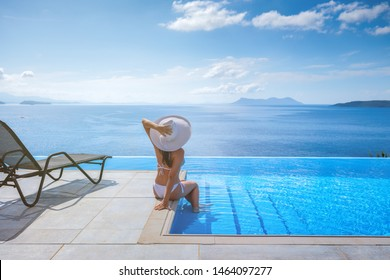 Beautiful view of the sea. In the foreground an infinity pool with a lounger and a young woman with a white hat who is relaxing