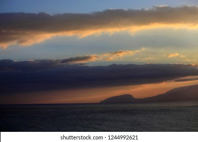Beautiful view of the sea, sky and clouds at sunset and silhouette of Bear Mountain in Crimea