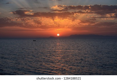 Beautiful view of the sea at sunset, the sun on the horizon and the rays in the clouds