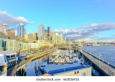 Beautiful view of Seattle waterfront and skyline at sunset. Marina at pier 66, port and great wheel (ferris wheel) can be seen in distance at far left corner. Travel and urban architecture background.