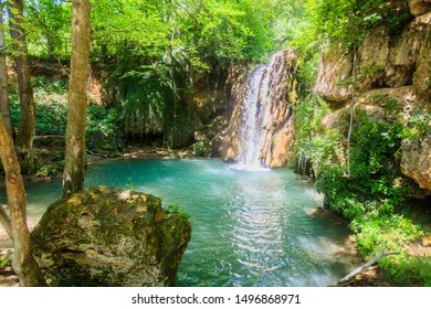 Beautiful view of secret place at summer day in forest waterfall , turquoise color water of natural pool.