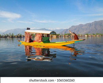 Beautiful view of Shikara boat ride on dal lake with houseboats and mountain background at Srinagar, Kashmir, India.