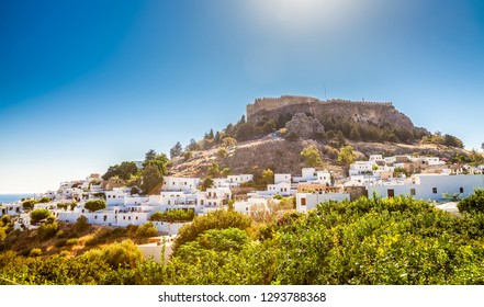 beautiful view with small white houses and the ancient Acropolis above, Lindos, Rhodes island, Greece