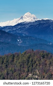Beautiful view of snow covered Mount Triglav, the highest peak in Slovenian Julian Alps on a bright sunny day, with hills and forest slopes in foreground