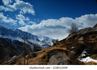 Beautiful View of snow covered mountains in front of a blue sky with clouds in Valle di Viso