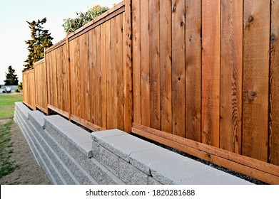 A beautiful view of a staggered retaining block wall of a residential property with a wooden fence  behind