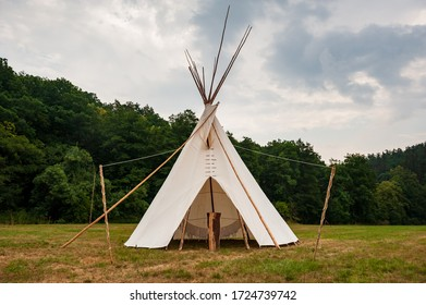 Beautiful view of the summer wedding tipi in a field. Tee pee built on green grass. Traditional teepee tent wigwam located in nature.