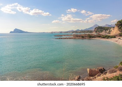A beautiful view of a sunny seaside with cliffs in Albir, Spain