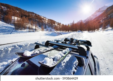 Beautiful view of sunny snowcapped mountains  with skis fastened on car roof rails in the foreground