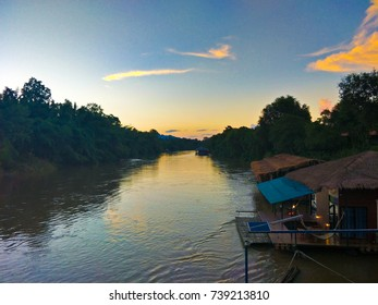 Beautiful view of sunset , orange and blue sky with house near river ,Thailand.