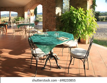 Beautiful view with tables and chairs at a open terrace cafe in italian village, Tuscany, Italy.