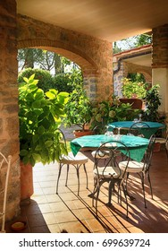 Beautiful view with tables and chairs at a open terrace cafe in italian village, Italy. Sun light