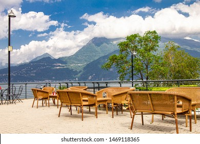 Beautiful view from terrace cafe of the overlooking the high mountains and shore lake Como. Empty wicker restaurant chairs are waiting for guests in a chic restaurant in the ancient city of Varenna.