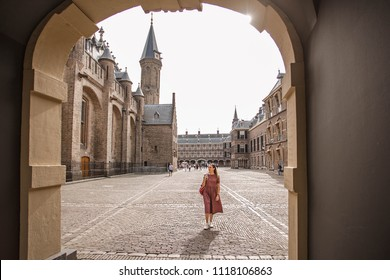 Beautiful view through the Arch to the medieval Binnenhof castle. Young woman walk in the Binnenhof palace courtyard. The Hague, The Netherlands.
