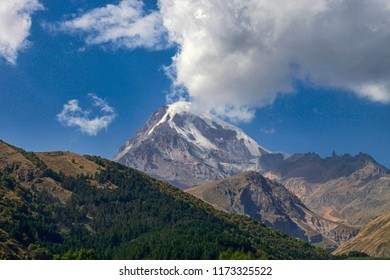 Beautiful view of the top of the mountain Kazbek in the snow against a background of blue sky and white clouds
