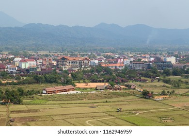 Beautiful view of town and fields from above in Vang Vieng, Vientiane Province, Laos, on a sunny day.
