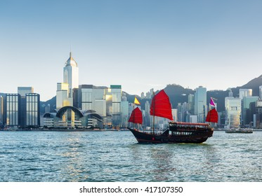 Beautiful view of traditional Chinese wooden sailing ship with red sails in Victoria harbor at evening. Skyscrapers in downtown of Hong Kong are visible from Kowloon side. The Hong Kong Island skyline