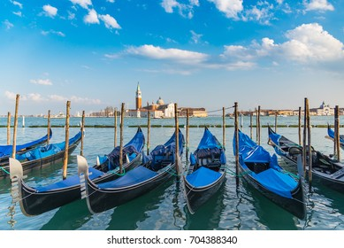The beautiful view of traditional Gondola boat on canal with historic Basilica di Santa Maria della Salute in the background on a sunny day blue sky in Venice, Italy