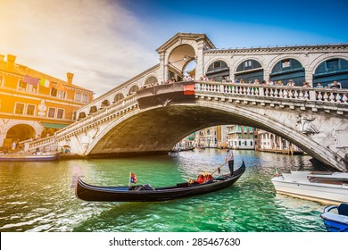 Beautiful view of traditional Gondola on famous Canal Grande with Rialto Bridge at sunset in Venice, Italy with retro vintage Instagram style filter and lens flare effect
