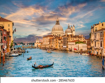 Beautiful view of traditional Gondola on famous Canal Grande with Basilica di Santa Maria della Salute in golden evening light at sunset in Venice, Italy