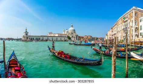 Beautiful view of traditional Gondola on Canal Grande with historic Basilica di Santa Maria della Salute in the background on a sunny day in Venice, Italy