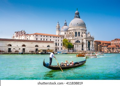 Beautiful view of traditional Gondola on Canal Grande near Piazza San Marco with historic Basilica di Santa Maria della Salute in the background on a sunny day with blue sky in summer, Venice, Italy