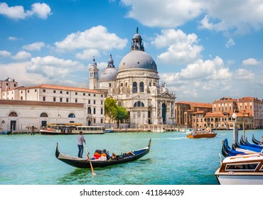 Beautiful view of traditional Gondola on Canal Grande near Piazza San Marco with historic Basilica di Santa Maria della Salute in the background on a sunny day with blue sky and clouds, Venice, Italy